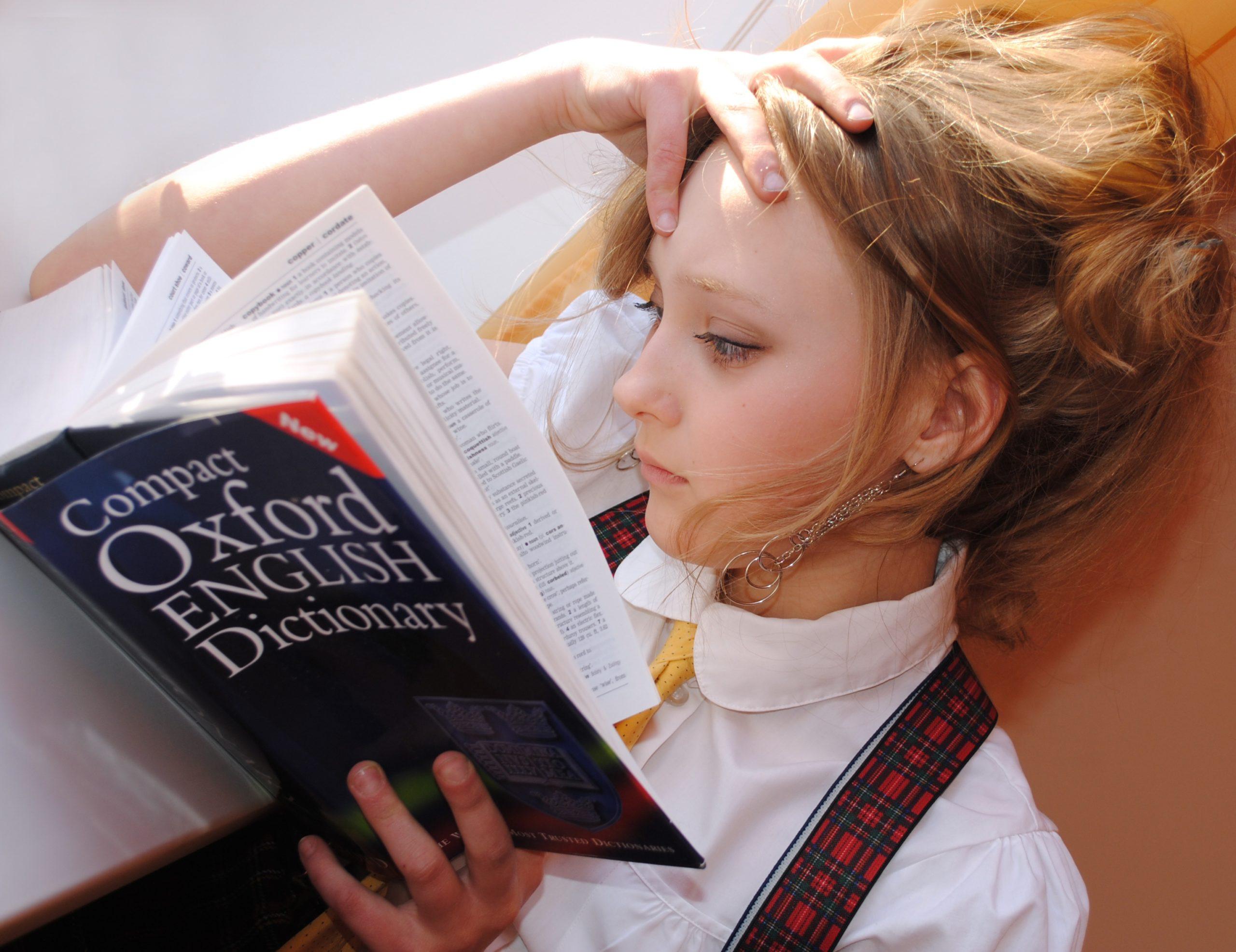 金髪の少女が英語辞書を読んでいる