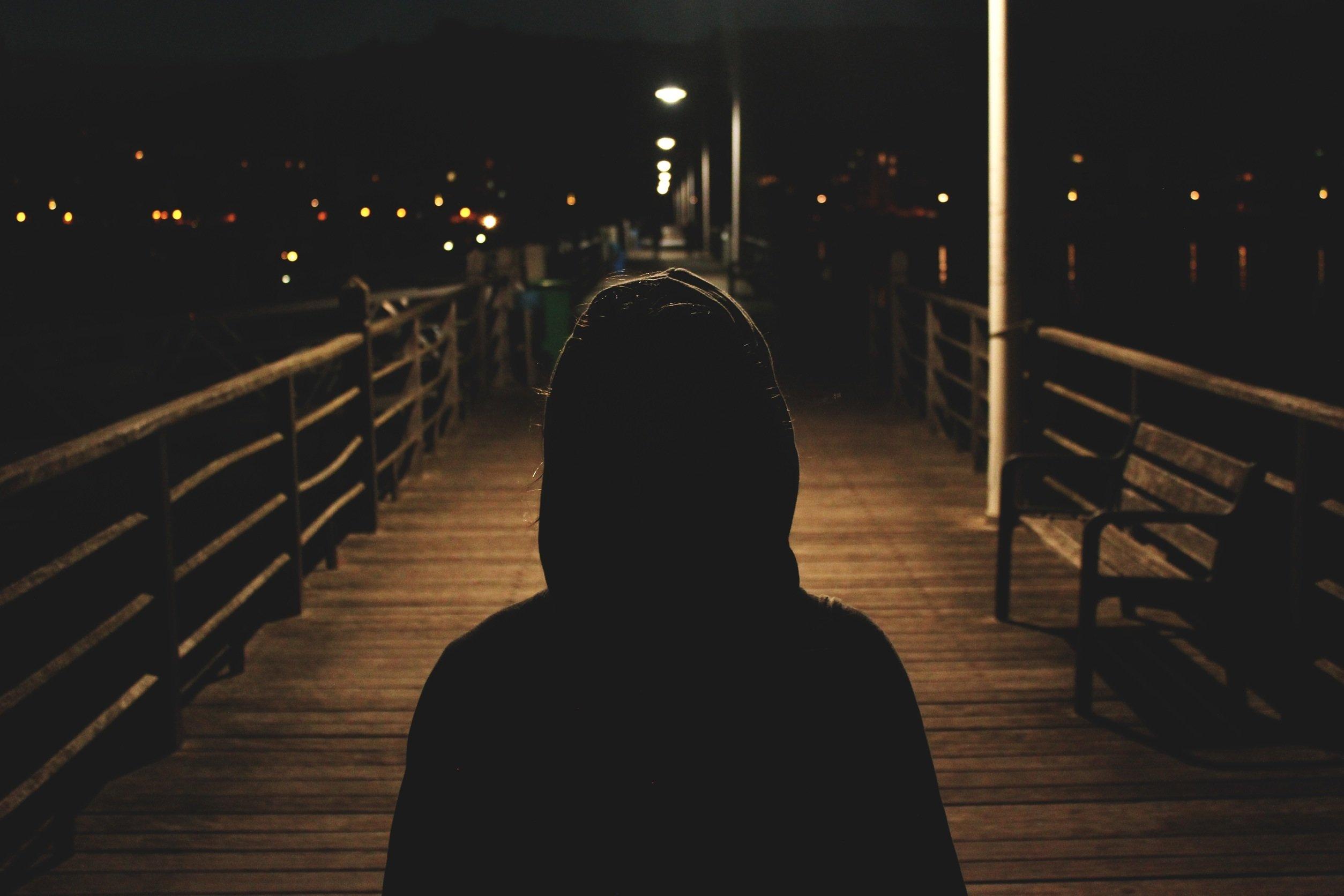 フードをかぶった男が暗い道の上で立っている画像