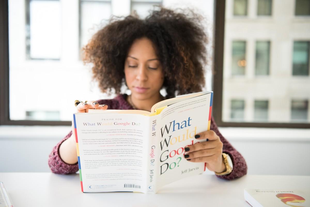 女性が窓際で本を読んでいる