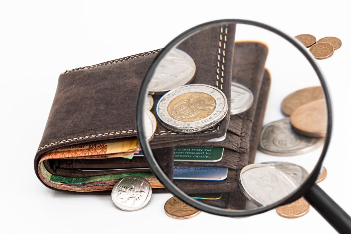 虫眼鏡でコインの溢れる財布を見ている画像