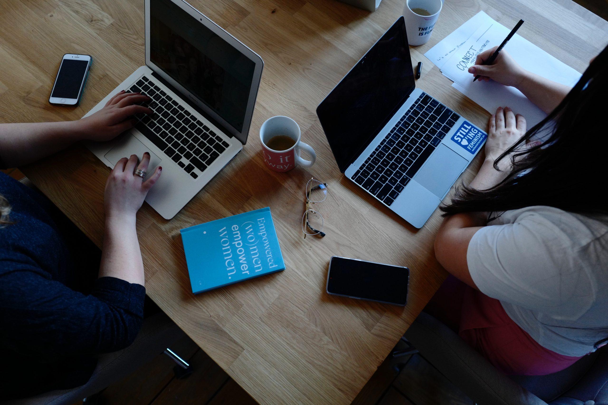 一つの机で二人の人間が二台のパソコンを使っている画像