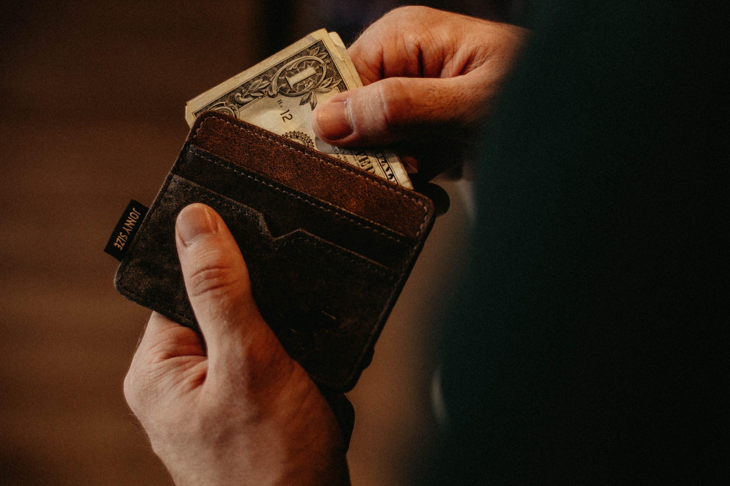 男性が財布からお札を取り出そうとしている